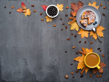 Seasonal autumn background. Frame of colorful maple leaves and a cup of hot drink, coffee, latte or cappuccino, nutmeg, cake, black currant and cinnamon over grey.