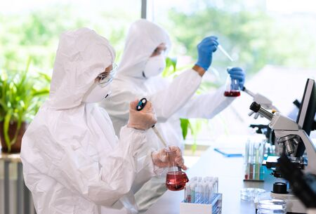 Scientists in protection suits and masks working in research lab using laboratory equipment: microscopes, test tubes. Imagens