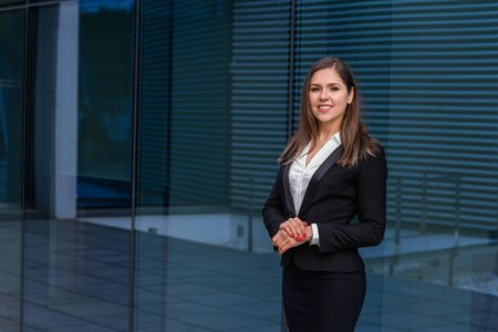 Confident businesswoman in front of modern office building. Business, banking, corporation and financial market concept. Stok Fotoğraf