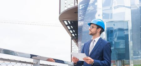 Real estate developer in helmet. New office construction. Confident business men or architect in front of office building.