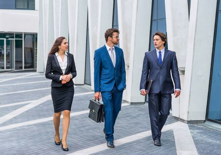 Confident businesspersons talking in front of modern office building. Businessmen and businesswoman have business conversation. Banking and financial market concept.