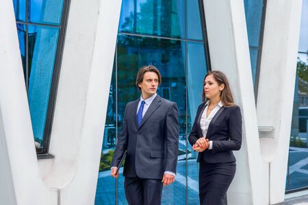 Confident businesspersons talking in front of modern office building. Businessmen and businesswoman have business conversation. Banking and financial market concept. Stok Fotoğraf - 130648209