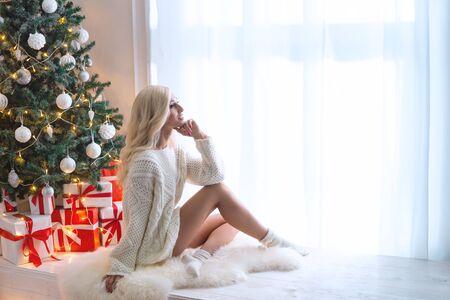Junge und schöne Frau im weißen Strickpullover, die allein zu Hause Weihnachten feiert. Attraktive Blondine vor dem Fenster und einem geschmückten Baum.