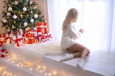Giovane e bella donna in maglione lavorato a maglia bianco che celebra il Natale a casa da solo. Bionda attraente davanti alla finestra e un albero decorato. Archivio Fotografico