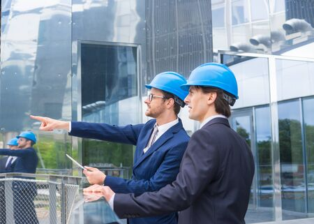 Real estate developers in helmets. New office construction. Confident business men and architect talking in front of modern office building.