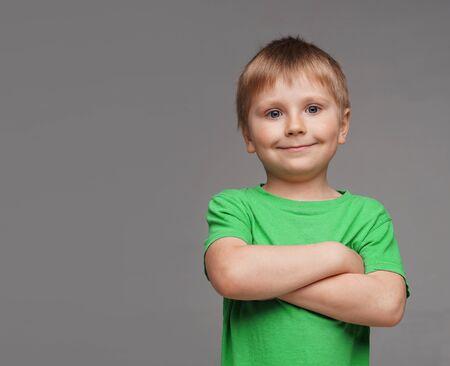 Portrait of happy smiling boy in green t-shirt. Attractive kid in studio. Childhood concept. Reklamní fotografie