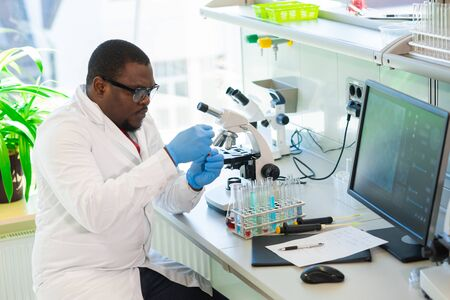 African-american scientist working in lab. Doctor making microbiology research. Laboratory tools: microscope, test tubes, equipment. Biotechnology, chemistry, bacteriology, virology and health care.