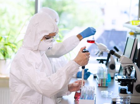 Scientists in protection suits and masks working in research lab using laboratory equipment: microscopes, test tubes. Stock fotó