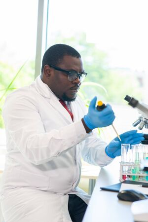 African-american scientist working in lab. Doctor making microbiology research. Laboratory tools: microscope, test tubes, equipment. Biotechnology, chemistry, bacteriology, virology, dna and health care concept.