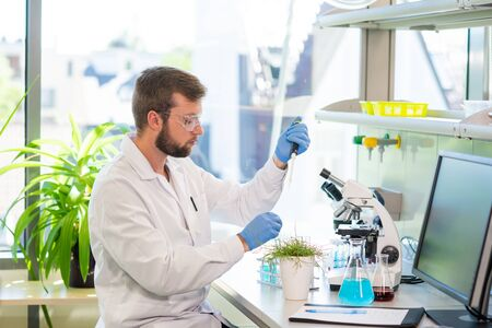 Scientist working in lab. Doctor making microbiology research. Laboratory tools: microscope, test tubes, equipment. Biotechnology, genetics, biochemistry, pharmaceutical, dna and health care. Stock fotó