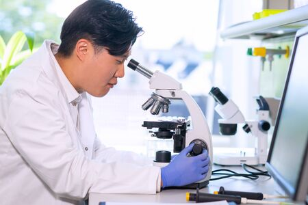 Asian medical doctor working in research lab. Science assistant making pharmaceutical experiments. Chemistry, medicine, biochemistry, biotechnology and healthcare.