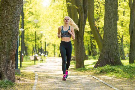 Mujer atractiva en entrenamiento de ropa deportiva al aire libre. Deporte, jogging, estilo de vida saludable y activo.