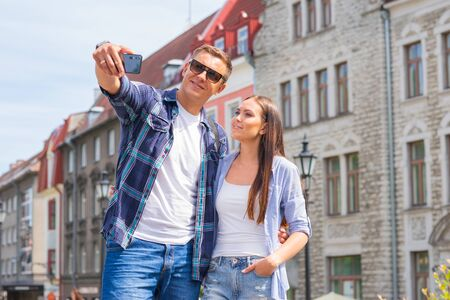 Couple of tourists traveling and exploring beautiful old town together. Loving man and woman in a vacation trip.