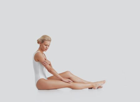 Young, beautiful, fit and natural blond woman in white swimsuit applying moisturizing cream. Massage, skin care, cellulite removal, sport and weight loss.