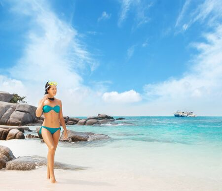 Young and beautiful woman in swimsuit relaxing on the beach. Girl having summer vacation in Thailand. Holidays and traveling.