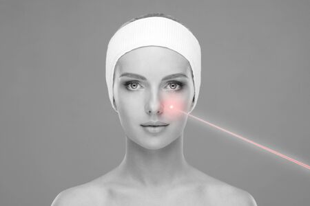 Doctor removing birthmarks with a laser ray. Beautiful face of a young woman. Mole removal, plastic surgery, skin lifting and aesthetic medicine. Stock Photo