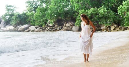 Elegant woman in white dress walking on the beach in Thailand. Holidays, traveling, vacation. Zdjęcie Seryjne