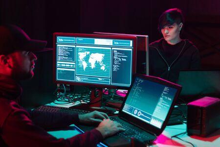 Internet fraud, darknet, data thiefs, cybercrime. Hacker attack on government server. Dangerous criminals coding virus programs in the basement.