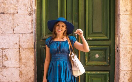 Young and beautiful brunette girl in dress and hat walking outdoor in the street. Nice, France. Summer vacation, traveling and tourism. 版權商用圖片