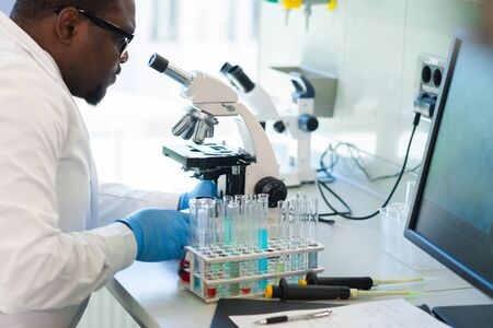 African-american scientist working in lab. Doctor making microbiology research. Laboratory tools: microscope, test tubes, equipment. Biotechnology, chemistry, bacteriology, virology and health care. Foto de archivo