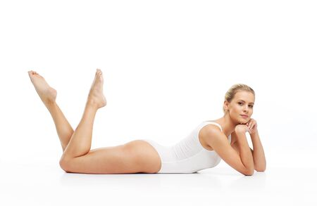 Young, beautiful, slim and healthy blond girl in white swimsuit applying skincare cream. Massage, skincare, healthcare, wrinkles removal and fitness.