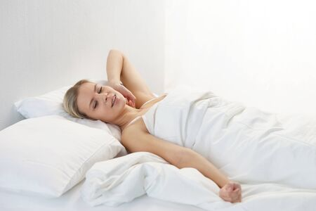 Young woman lying in the bed. Beautiful blond sleeping girl. Morning in the bedroom, daylight from the window. Health and rest. Standard-Bild
