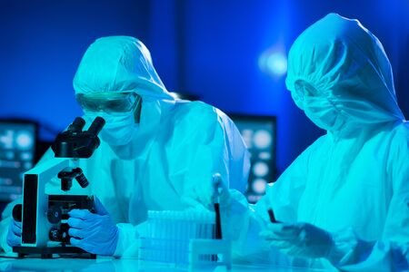 Scientists in protection suits and masks working in research lab using laboratory equipment: microscopes, test tubes. Coronavirus covid-19 hazard, pharmaceutical discovery, bacteriology and virology.