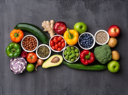 Healthy eating ingredients: fresh vegetables, fruits and superfood. Nutrition, diet, vegan food concept. Concrete background