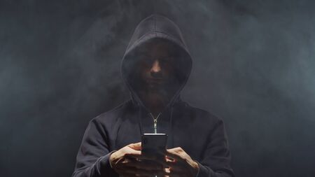 Portrait of computer hacker in hoodie. Obscured dark face. Data thief, internet fraud, darknet and cyber security . Stockfoto