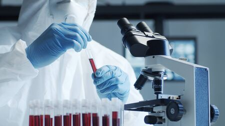 Scientist in protection suit and masks working in research lab using laboratory equipment: microscopes, test tubes. Coronavirus 2019-ncov hazard, pharmaceutical discovery, bacteriology and virology.