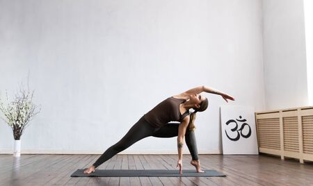 Young and fit woman practicing yoga indoor in the class. Stretching exercise in the day light. Sport, fitness, health care and lifestyle concepts. Stock fotó
