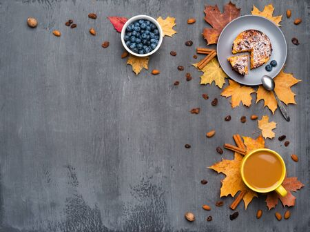 Seasonal autumn background. Frame of colorful maple leaves and a cup of hot drink, coffee, latte or cappuccino, nutmeg, cake, blueberries and cinnamon over grey.