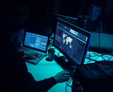 Internet fraud, darknet, data thiefs, cybercrime concept. Hacker attack on government server. Dangerous criminals coding virus programs in the basement.