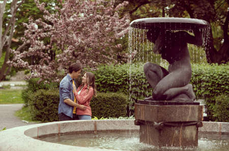 Young, happy, loving couple having date in the park near fountain. Relations, friendship and love. Stockfoto
