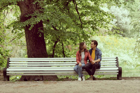 Young, happy, loving couple having date on the bench in the park. Relations, friendship and love.