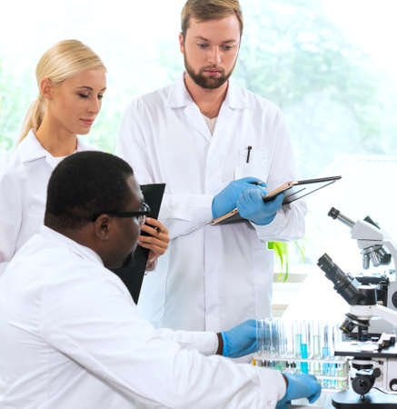 Scientist and students working in lab. Doctor teaching interns to make blood analyzing research. Biotechnology, chemistry, bacteriology, virology and health care concept. Stockfoto