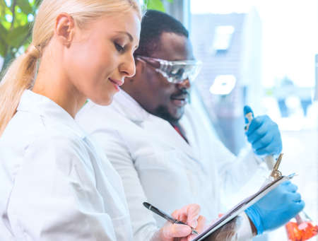 Scientist working in lab. Doctors making medical research. Laboratory tools: microscope, test tubes, equipment. Coronavirus, chemistry, science, experiments and healthcare concept.