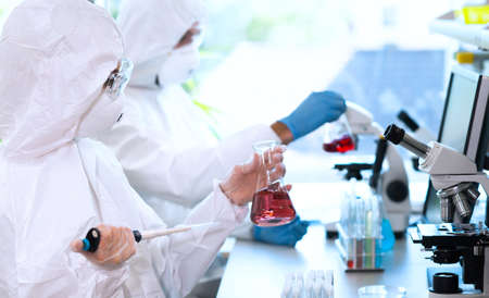 Scientists in protection suits and masks working in research lab using laboratory equipment: microscopes, test tubes. Stockfoto