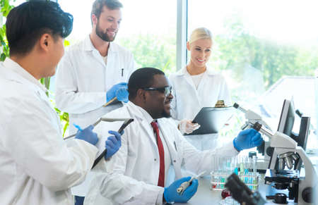 Scientist and students working in lab. Doctor teaching interns to make blood analyzing research. Biotechnology, chemistry, bacteriology, virology and health care concept. Zdjęcie Seryjne