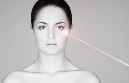 Removing birthmarks with a laser ray. Beautiful face of a young woman. Standard-Bild