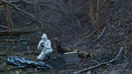 Detectives are collecting evidence in a crime scene. Forensic specialists are making expertise. Police investigation in a forest. Zdjęcie Seryjne