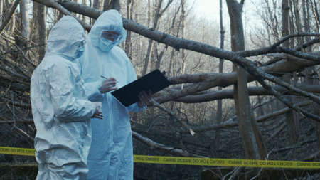 Detectives are collecting evidence in a crime scene. Forensic specialists are making expertise. Police investigation in a forest. Archivio Fotografico