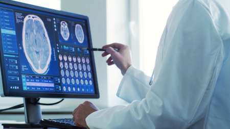 Professional medical doctor working in hospital office using computer technology. Medicine, neurosurgery and healthcare.