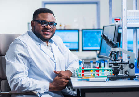 Professional African-American scientist is working on a vaccine in a modern scientific research laboratory. Genetic engineer workplace. Future technology and science.