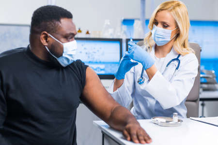 Professional doctor makes a coronavirus vaccine using a syringe and hypodermic needle. Professional medical worker and patient at the hospital office. Vaccination and safety.