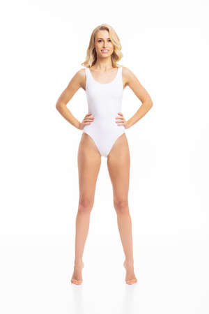 Young, fit and beautiful blond woman in white swimsuit isolated on white. Healthcare, diet, sport and fitness concept.