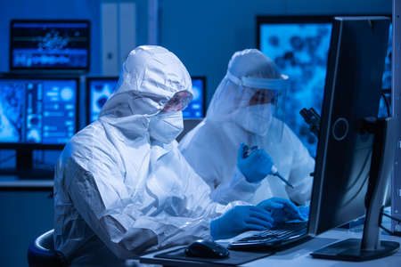 Professional team of scientists is working on a vaccine in a modern scientific research laboratory. Genetic engineer workplace. Future technology and science concept.