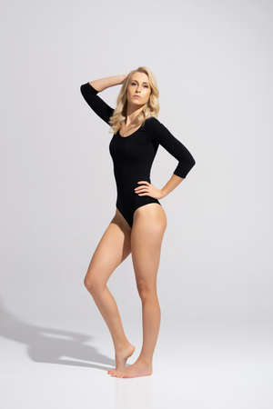 Young, fit and beautiful blond woman in black swimsuit posing over grey background. Healthcare, diet, sport and fitness.