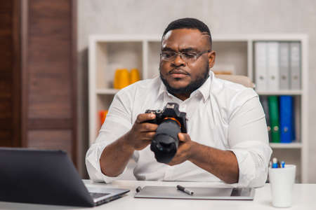 Freelance photographer workplace at home office. Young African-American man works using a computer, graphics tablet and other devices. Remote job.