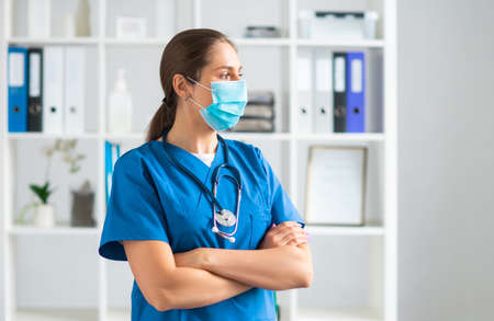 Professional medical doctor working in hospital office, Portrait of young and attractive female physician in protective mask. Archivio Fotografico